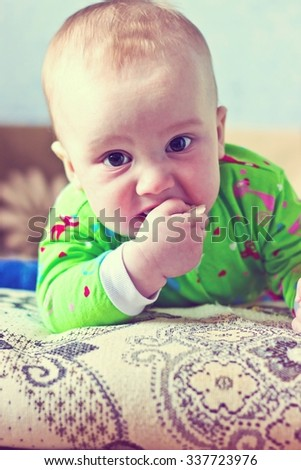 Portrait of adorable serious baby boy eating cabbage and looking at camera. Vertical image with vintage filter - stock photo