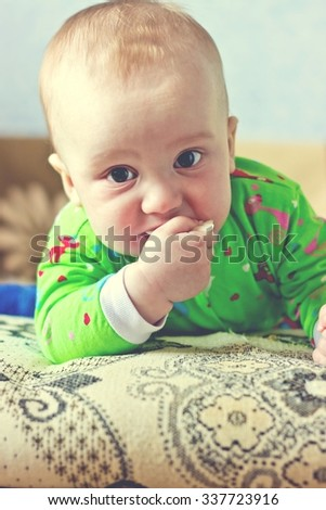 Portrait of adorable serious baby boy eating cabbage and looking at camera. Vertical vintage image - stock photo