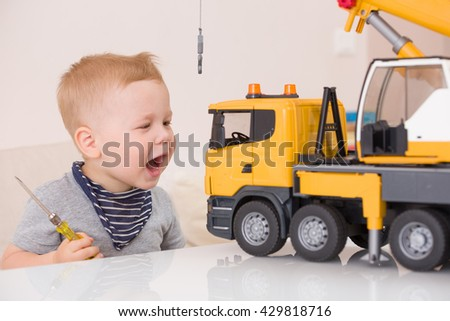 Portrait of adorable smiling toddler boy playing with a big construction car at home. Little child repairing his toy car. Educative toys for children. Early learning,developing concept - stock photo