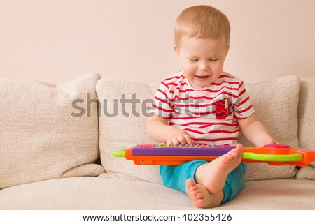 Portrait of adorable toddler boy sitting on the sofa and playing toy piano. Early learning at home. Little musician. Child and toys.Education. Indoors. - stock photo