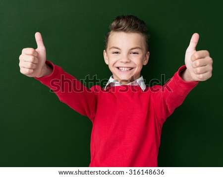 Portrait of adorable young boy showing thumbs up sign using both hands at the dark green chalkboard in classroom. - stock photo