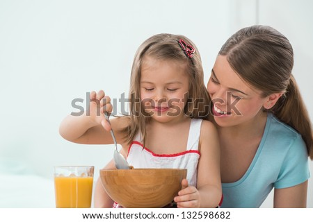 Portrait of adorable young girl and mother in a playful mood having breakfast at home - stock photo