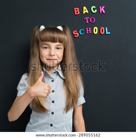 Portrait of adorable young girl showing thumb up sign at the black chalkboard in classroom. - stock photo
