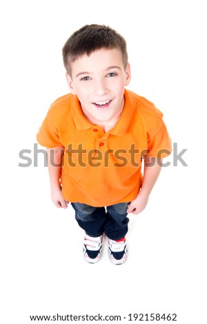 Portrait of adorable young happy boy looking up in orange t-shirt. Top view. Isolated on white background.