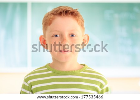 Portrait of adorable young student looking at camera in front of blackboard. - stock photo