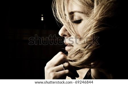 Portrait of adult attractive woman indoor in dark room - stock photo