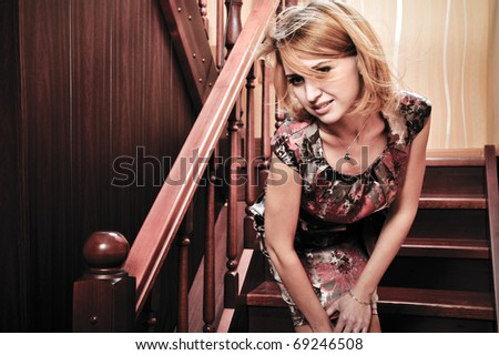 Portrait of adult attractive woman indoor waiting on stairs at home for her valentine - stock photo