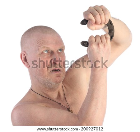 portrait of adult bald man with a naked torso trying to straighten a horseshoe on a white background studio