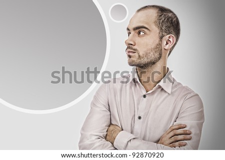 Portrait of adult businessman posing against grey background. Blank balloon with copyspace for your text and logo - stock photo