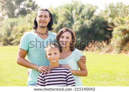 Portrait of adult couple with teenage son  in sunny park