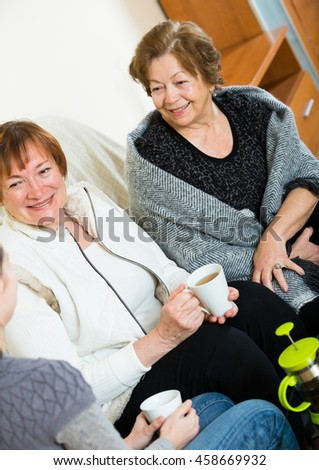 Portrait of adult girl and two pensioners drinking tea together - stock photo
