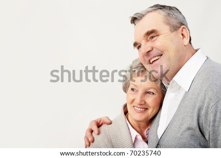 Portrait of adult man embracing her wife with love over white background