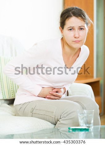 Portrait of adult russian girl folding up with belly pain indoor