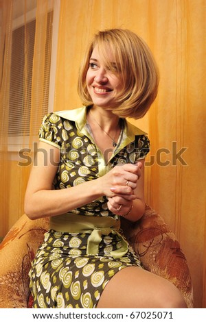 Portrait of adult smiling woman against orange wall at background - stock photo