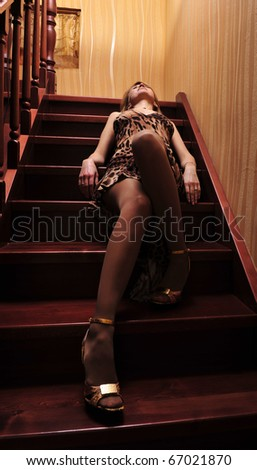 Portrait of adult woman posing on camera laying on wooden stairs indoor - stock photo