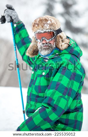 Portrait of adventure man with extreme explorer gear in stormy snow weather. Active healthy lifestyle concept - stock photo