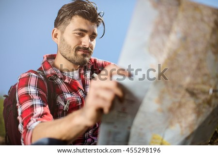 portrait of adventure man with map  on mountain with sunrise or sunset - stock photo