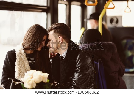 Portrait of affectionate couple in the city bus - stock photo