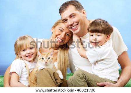 Portrait of affectionate family members on blue background - stock photo