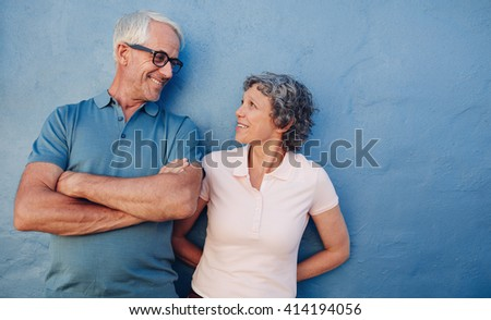 Portrait of affectionate mature couple looking at each other against blue background. Loving middle aged man and woman standing together against a blue wall. - stock photo