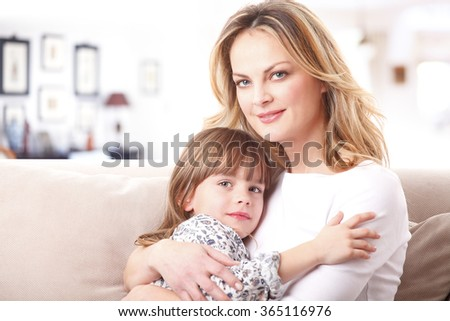Portrait of affectionate mother hugging her daughter while sitting on sofa at home.