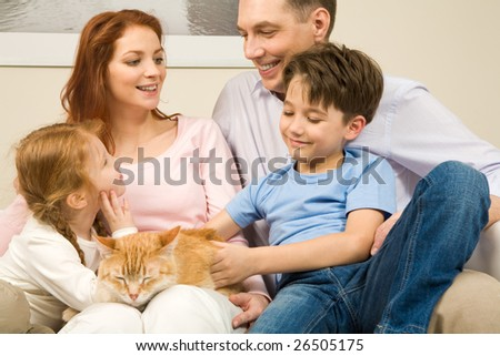 Portrait of affectionate parents and their children enjoying weekend day at home - stock photo