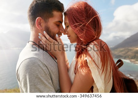 Portrait of affectionate young couple about to kiss. Romantic young man and woman sharing a lovely moment on their summer vacation.