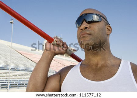 Portrait of African American athlete about to throw javelin - stock photo