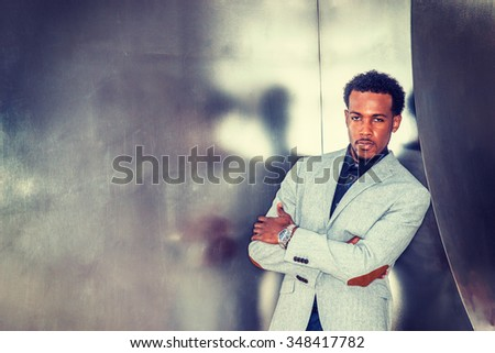 Portrait of African American Businessman in New York. Wearing gray patterned blazer, wristwatch, crossing arms, a black man with beard standing against silver metal wall. Instagram filtered look. - stock photo