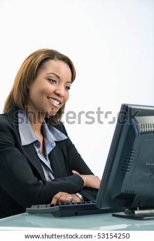 Portrait of African American businesswoman sitting at office desk smiling and looking at computer monitor.