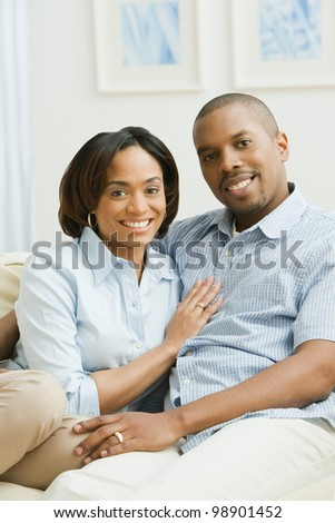 Portrait of African American couple on sofa - stock photo