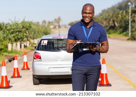 portrait of african american driving instructor writing on clipboard - stock photo
