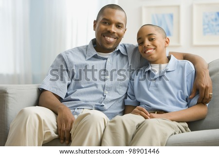 Portrait of African American father and son on sofa - stock photo