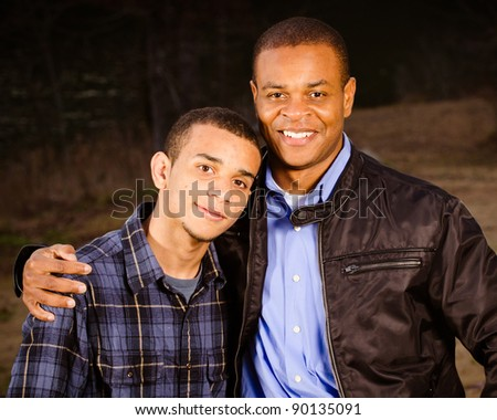 Portrait of African-American father and teenage son outdoors at park - stock photo