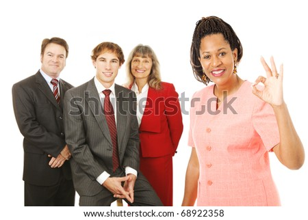 Portrait of african-american female business woman with her team, giving the Okay sign.  Isolated on white.