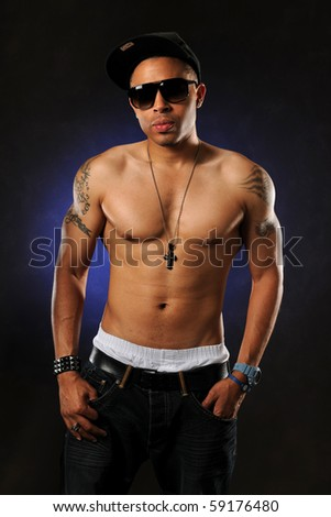 portrait of African American hip hop man without a shirt standing over dark background - stock photo