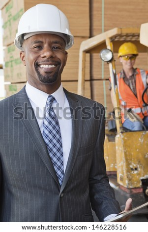 Portrait of African American male engineer smiling with female worker in background