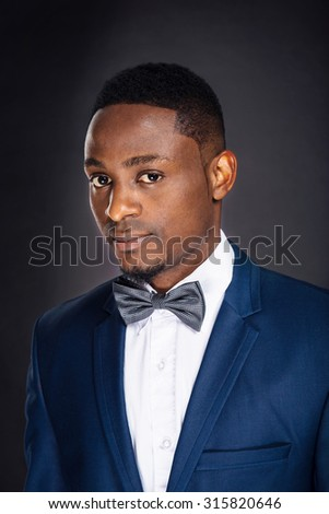 Portrait of african american successful businessman on black background