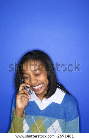 Portrait of African-American teen girl talking on cellphone smiling standing in front of blue background.