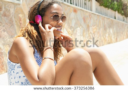 Portrait of african american teenager girl using headphones to listen to music, smiling having fun, trendy teenager outdoors. Adolescent technology lifestyle, home exterior suburban street. - stock photo