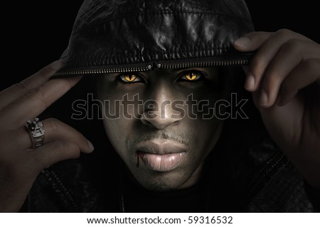 Portrait of African American vampire with hood over head with strong directional light - stock photo