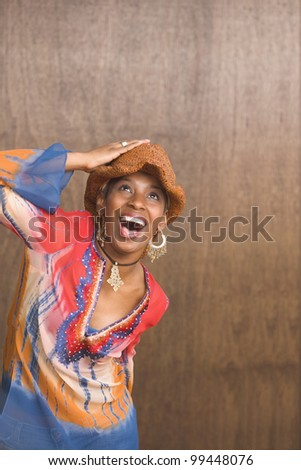 Portrait of African American woman holding hand on hat looking up - stock photo