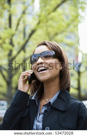 Portrait of African American woman wearing sunglasses and smiling talking on cellular phone. - stock photo