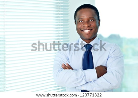 Portrait of African businessman looking at camera with smile - stock photo
