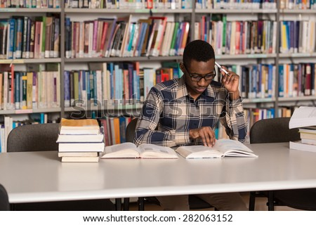 Portrait Of African Clever Student With Open Book Reading It In College Library - Shallow Depth Of Field - stock photo