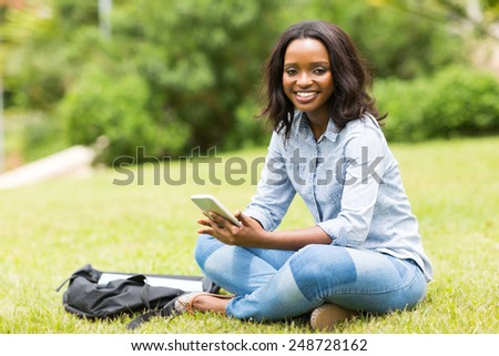portrait of african college girl sitting at the park - stock photo