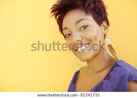 portrait of african college student with earrings smiling at camera with yellow wall in background. Head and shoulders, copy space