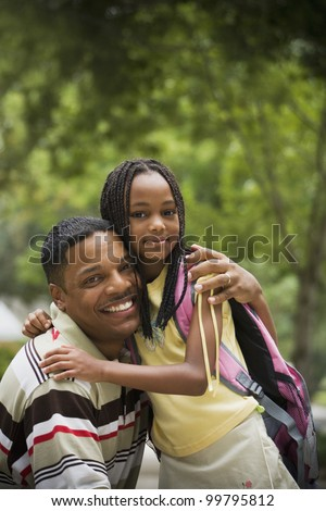 Portrait of African father and daughter hugging - stock photo