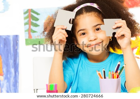 Portrait of African girl holding puzzle pieces - stock photo