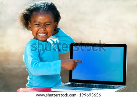 Portrait of African girl with funny face expression pointing at blank laptop screen. - stock photo